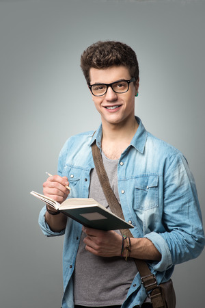 college student: Confident college student reading a book and holding a pencil Stock Photo