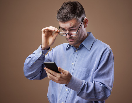 eyesight: Businessman adjusting his glasses while reading messages on his smartphone Stock Photo
