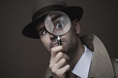 Grappige vintage detective kijken door een vergrootglas Stockfoto