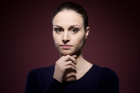 insecure: Pensive young woman posing with hand on chin Stock Photo