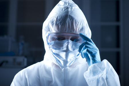 protective suit: Researcher wearing hazmat protective suit and safety goggles.