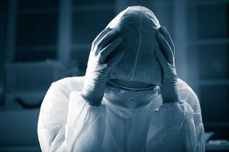 hazmat: Terrified scientist head in hands wearing hazmat protective suit. Stock Photo