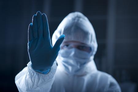 hazmat: Scienziato con sollevato in tuta protettiva hazmat mano, stop concetto.