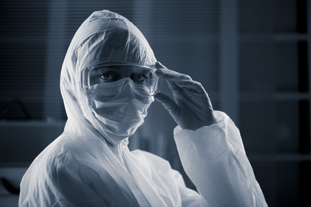 infective: Researcher wearing hazmat protective suit and safety goggles.