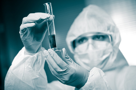 infective: Scientist wearing protective suit and examining a test tube.