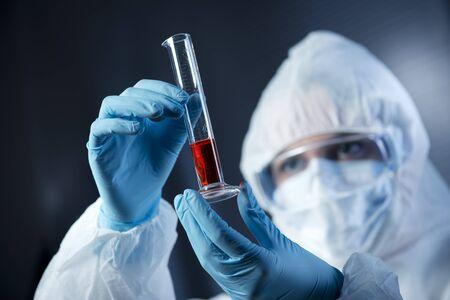 riesgo quimico: Científico vistiendo traje de protección y examinar un tubo de ensayo.