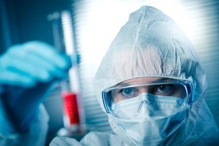 hazmat: Ricercatore in hazmat tuta protettiva l'esame di una provetta in laboratorio chimico.