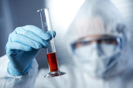 infective: Investigador en traje de protecci�n de materiales peligrosos examen de un tubo de ensayo en el laboratorio de qu�mica.