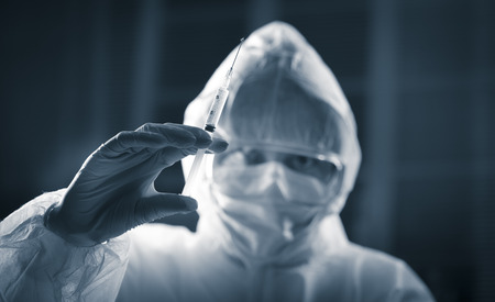 infective: Researcher in hazmat protective suit preparing a syringe for injection. Stock Photo