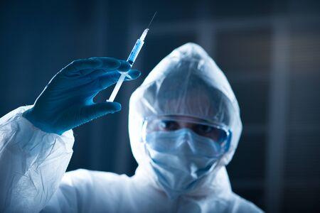 protective suit: Researcher in hazmat protective suit preparing a syringe for injection. Stock Photo