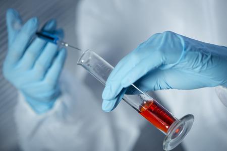 riesgo quimico: Investigador en seguridad traje de materiales peligrosos preparar una jeringa para inyección con el tubo de ensayo de vidrio.