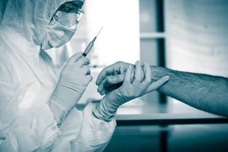 Doctor injecting medication on patients arm using a syringe. photo