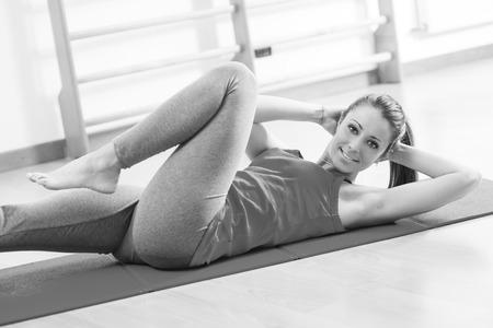 flat stomach: Mujer atractiva que hace ejercicios abdominales en el gimnasio para tonificar los músculos y vientre plano. Foto de archivo