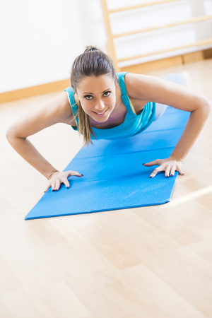 Woman doing push-ups at gym on a mat for muscle toning and weight loss.