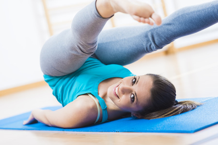Woman doing pilates workout at gym for muscle toning and weight loss.