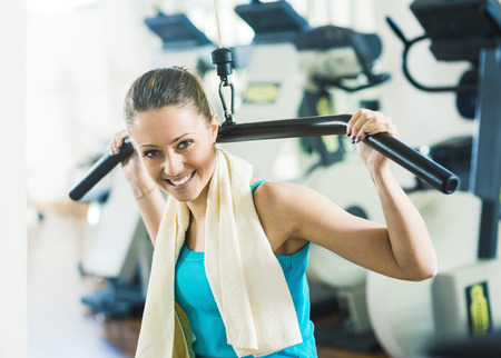 human energy: Attractive woman exercising at gym, biceps workout on a machine.