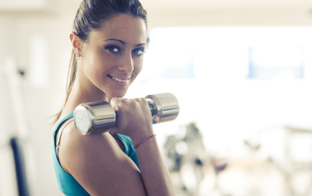 tricep: Attractive smiling woman doing weightlifting exercise at gym with dumbbells. Stock Photo