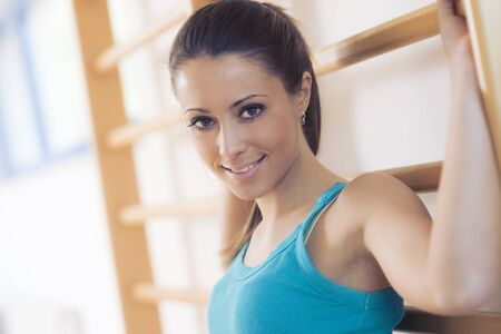 skinny woman: Attractive smiling woman at gym leaning against wood wall bars.