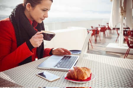 open air: Woman drinking a cappuccino at the cafe and working on her laptop on a open air terrace