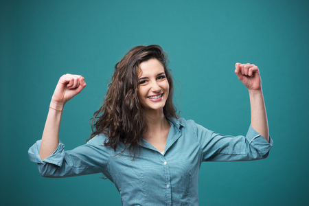tough girl: Cheerful young woman smiling with raised fists