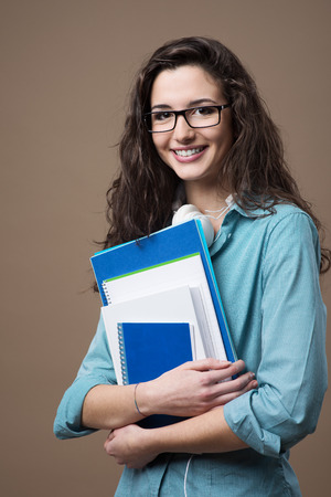 Beautiful young teenager girl student posing with notebooks and smiling at camera Stok Fotoğraf