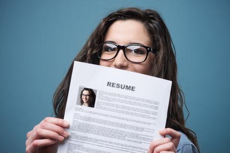 interview job: Mujer que oculta detr�s de su joven curr�culum Foto de archivo