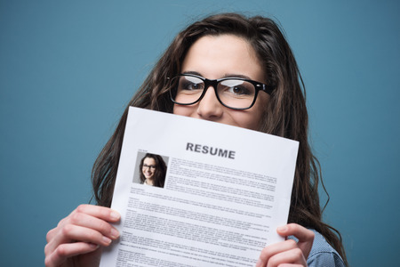 Young woman hiding behind her resume Stock Photo - 37460770