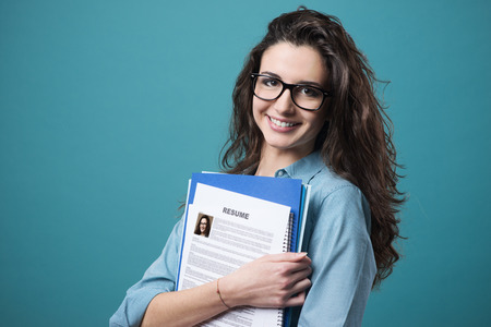 Young smiling cheerful woman holding her resume 스톡 콘텐츠