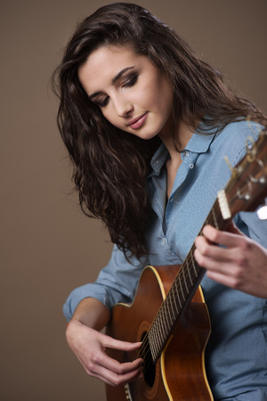 girl pose: Young female guitarist performing with acoustic guitar Stock Photo