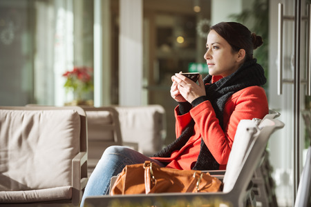 Attractive woman relaxing at the cafe and drinking an hot coffee photo