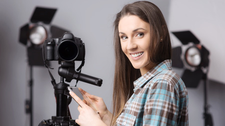 cameras: Young female photographer posing with a digital camera on tripod and lighting equipment on background