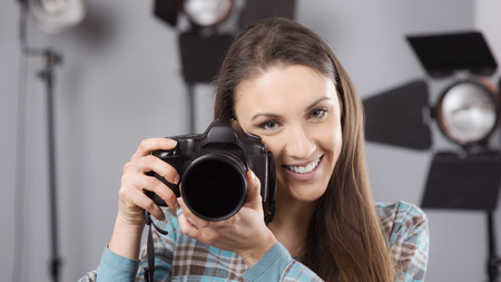 lighting equipment: Young female photographer posing in her professional studio, holding a digital camera with lighting equipment on background
