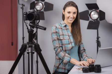 Female photographer working in her professional photo studio with a laptop, camera and lighting equipment Фото со стока