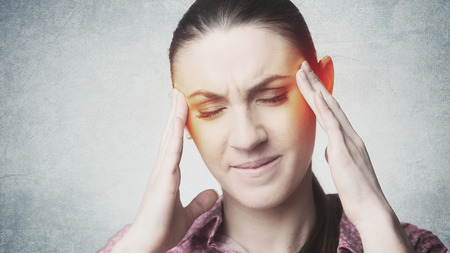 overburdened: Sad frowning woman with headache touching her temples Stock Photo