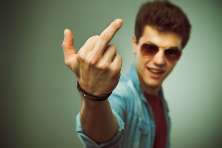 middle finger: Confident smiling teenager in sunglasses showing middle finger Stock Photo