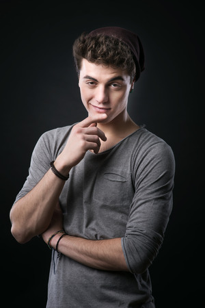 raised eyebrows: Smirking young attractive man posing with hand on chin