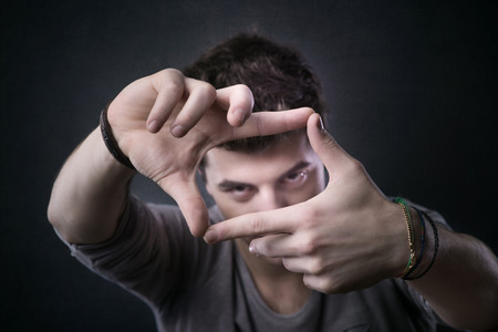 flirty: Young handsome flirty man making a frame with his fingers around his eyes Stock Photo