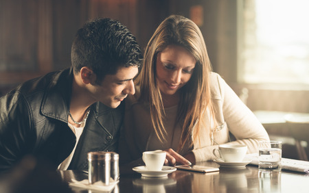 Man and woman at the bar having a coffee and using a mobile phone photo