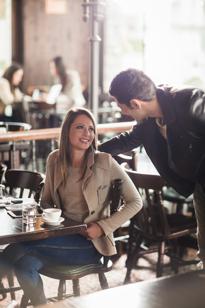 arriving: Beautiful smiling woman and stylish man meeting at the bar, he is touching her back Stock Photo