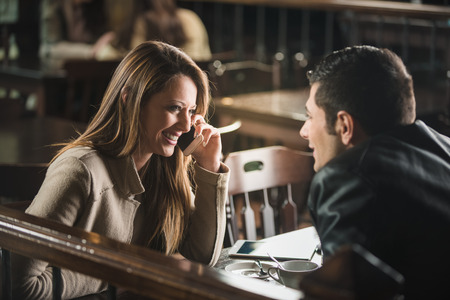 Young cheerful man and woman dating and spending time together at the bar