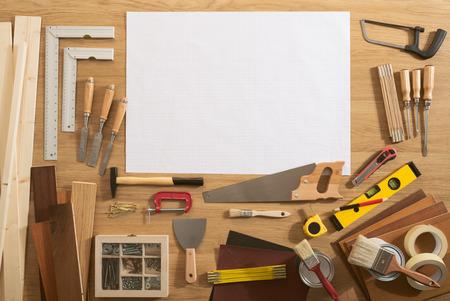 herramientas de carpinteria: Proyecto de bricolaje en blanco con las herramientas de espacio de la copia y de la construcción a su alrededor en una mesa de trabajo, vista desde arriba
