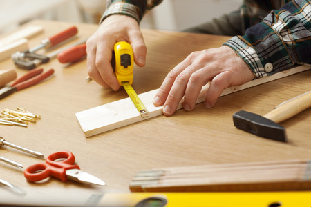 Man working on a DIY project and measuring a wooden plank with work tools all around, hands close up photo