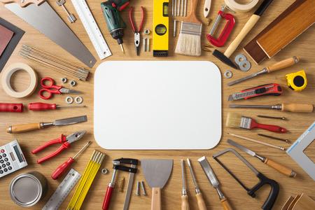 herrajes: Banner de bricolaje y mejoras para el hogar con las herramientas de trabajo y de la construcción de una visión superior de madera mesa de trabajo, muestra blanca en blanco en el centro Foto de archivo