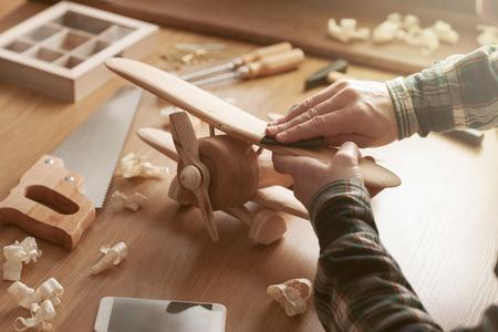 artesano: Craftsman alisar una superficie de juguete de madera con papel de lija, herramientas y virutas de madera por todas partes, las manos se cierran para arriba