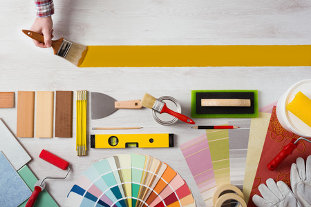 Decorator holding a paint brush and painting a wooden surface, work tools and swatches at bottom, banner with copy space