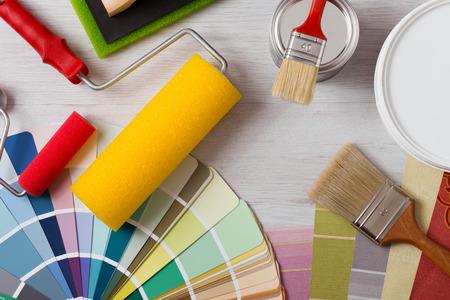 festékek: Festő és dekoratőr munkaasztal ház projekt, színtárak, festés görgős és ecsetek, felülnézet Stock fotó