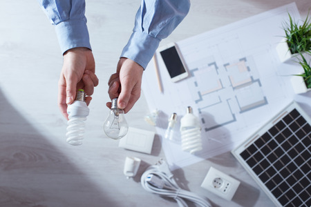 electricity generator: Man comparing an obsolete incandescent bulb and a CFL energy saving lamp, house project and solar panel