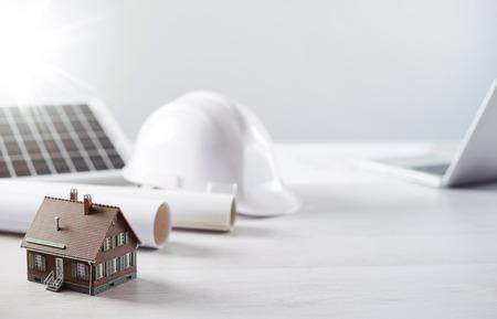 ahorro energia: Ingeniero estructural y de escritorio arquitecto con casco de seguridad, el panel solar y la casa modelo Foto de archivo