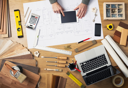 Construction engineer and architects desk with house projects, laptop, tools and wood swatches top view, male hands using a digital tablet Фото со стока