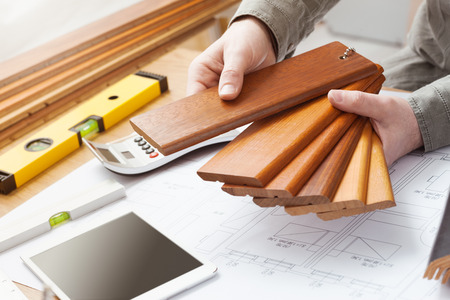 Professional interior designer holding wood swatches for baseboard and skirting, hands close up with desktop, house blueprint, tools and tablet